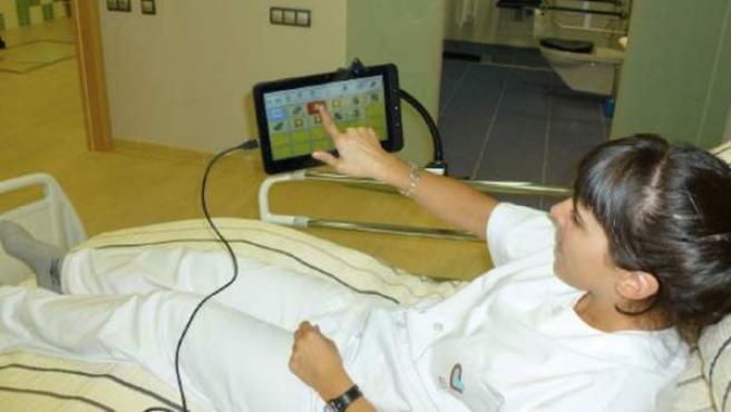 Persona usando un aparato tecnológico domotizado en su vivienda